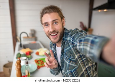 Boasting with a new meal. A smiling man making selfie on his kitchen