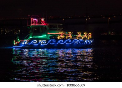 Boat Adorned with Christmas Holiday Lights, Santa Claus Sleigh and  Reindeer and Reflection in the Water.