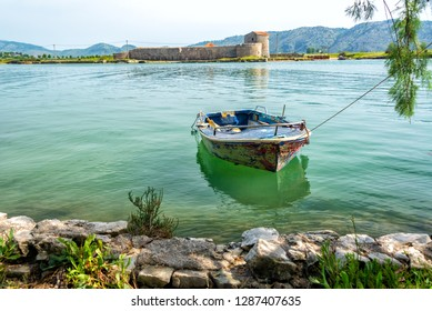 Boat with Ali Pasha's castle in the background in Butrint, Albania
