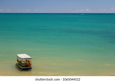 Boat alone on tropical beach. Turquise blue water, waterline and blue sky. Alagoas, Brazil.