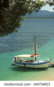 Boat anchored near sandy beach in Mediterranean sea