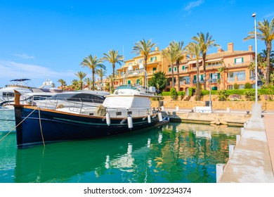 Boat anchoring in Sotogrande marina with colorful houses, Andalusia, Spain
