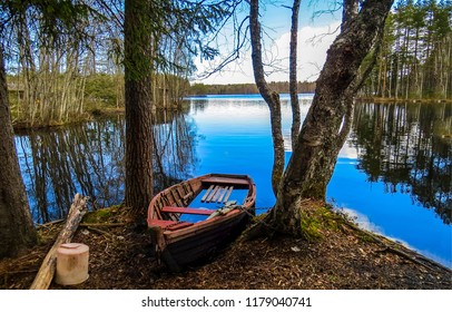 Boat at autumn forest river shore scene. Forest river shore boat scene. Boat at forest river shore view