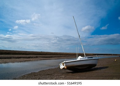 A boat at Blakeney Harbour in Norfolk, England on slipway against a blue sky