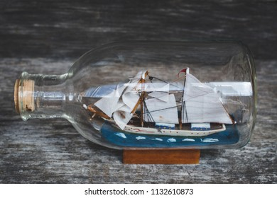 boat in the bottle on wooden table