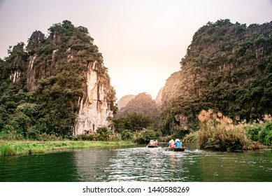 Boat cave tour in Trang An Scenic Landscape formed by karst towers and plants along the river (UNESCO World Heritage Site). It's Halong Bay on land of Vietnam. Ninh Binh province, Vietnam.