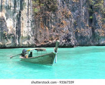 Boat in clear blue water with rocks in background.