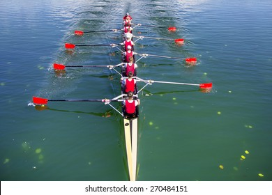 Boat coxed eight Rowers rowing on the blue lake