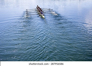 Boat coxed eight Rowers rowing on the tranquil blue lake