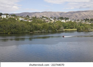 Boat cruising down the Snake River between the adjoining cities of Lewiston, Idaho and Clarkston, Washington