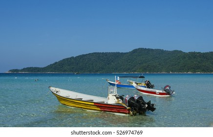 Boat at crystal clear waters Perhentian Kecil Island beach, Terengganu, Malaysia.