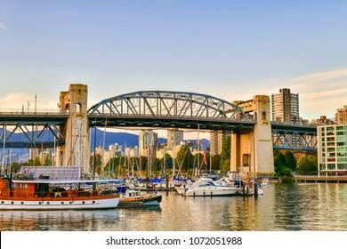 Boat docked along in Granville island near Burrard Street Bridge at twilight in Vancouver,Canada