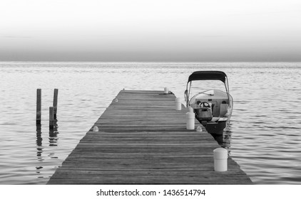 Boat docked at the jetty at sunrise in stunning black and white