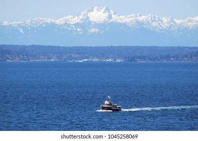 Boat driving along in front of Olympic Mountains on Elliott Bay in Seattle