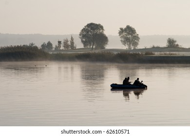 Boat with fishermen in the fog on the lake