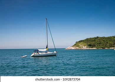 A boat floating in the sea, heading towards the shore on a bright sky day