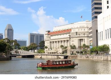 Boat in front of Cavenagh bridge and Fullerton Building, Singapore