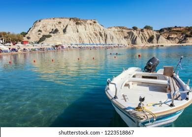 Boat in front of umbrellas, sunbeds on Kolymbia beach (Rhodes, Greece)
