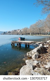 Boat in frozen lake Orestiada, old wooden pier and Kastoria city as background