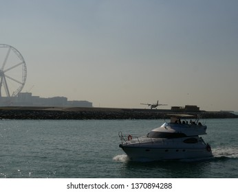 Boat heading for port with hangar and spike wheel in the background