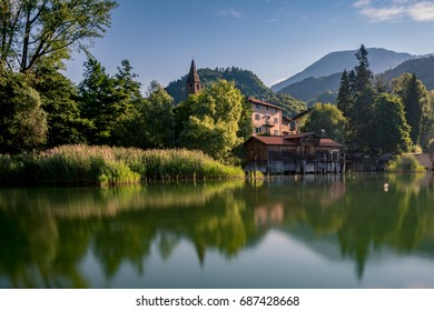 Boat house reflected on a calm lake in a Italian mountain landscape with the tower of an ancient church on the background