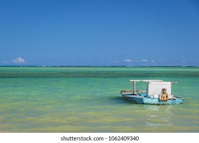 A boat (jangada) floats alone in clear water on the paradisiacal beach of São Miguel dos Milagres, Alagoas, Brazil.