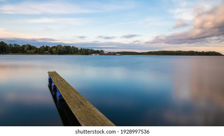 Boat jetty on a lake with blue cloudy sky as long time shot