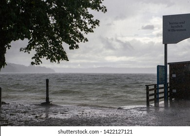 Boat launch on the Ammersee in Bavaria in front of a sky with thunderstorm atmosphere German Text Good day and welcome
