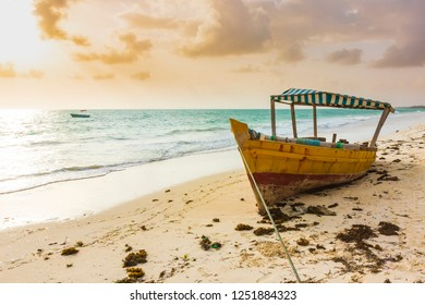 Boat laying dry, stranded on a tropical beach during sunset at Zanzibar, Tanzania