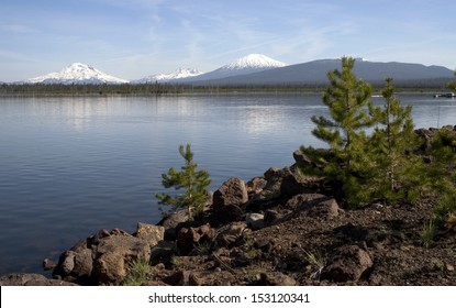 A boat lays on the dock on lake in the Cascade Range of Oregon with Mt. Broken Top and Mt Bachelor in the distance