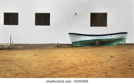 Boat leaning against a white wall