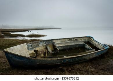 A boat lies, decrepit on a misty beach