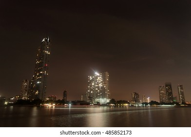 Boat Light Trails Along Chao Phraya River in Bangkok with a View of Buildings at Night