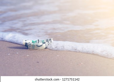 A boat made of paper money in the sea sand A boat out of the dollar in the sea. Sea sand. Concept for the dollar. Copy space. Toning