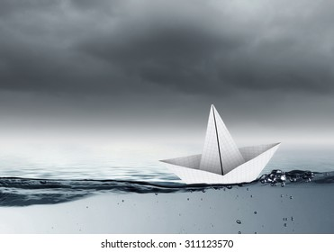 Boat made of paper sailing on blue water surface