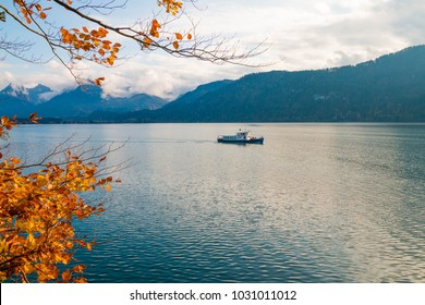 Boat makes its way through alpine lake Wolfgangsee from St.Wolfgang to St.Gilgen. Beutiful autumn in austrian alps.