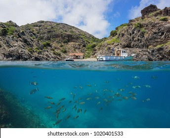 Boat moored near a cove with a fishermen hut and a shoal of fish underwater, split view above and below water surface, Cap de Creus, Mediterranean sea, Spain, Costa Brava, Catalonia, Cala Gentil