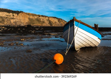 A boat moored on a beach at low tide in the sunshine with cliffs in the background and an orange buoy in the foreground.