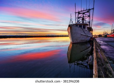 Boat moored on the calm river, against the vibrant sunset