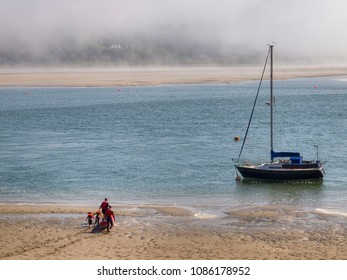 A boat moored on the River Mawddach estuary at Barmouth, Wales. Sea mist rolls in.