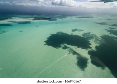 Boat moves between island keys in tropical waters off the coast of Belize