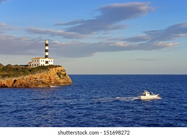 Boat navigating near an ancient lighhouse in spain