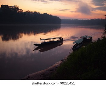 A boat navigating the Tambopata jungle river during a purple and pink sunrise with reflection in the water in the Amazon rainforest in eastern Peru.