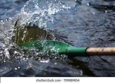 boat oar in the water and splashing water