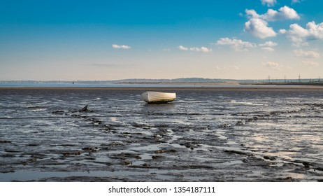 A boat in the Oare Marshes with the North Sea coast of Kent in the background, near Faversham, Kent, England, UK
