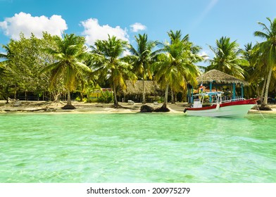Boat on azure water on a background of exotic beach on one of the Caribbean Islands