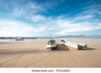 Boat on the beach with blue sky.