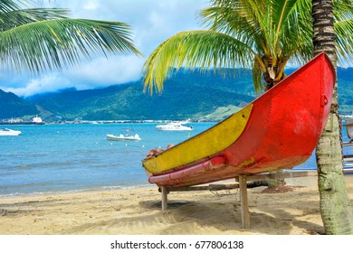 Boat on the beach with coconut tree and sea in Ilhabela