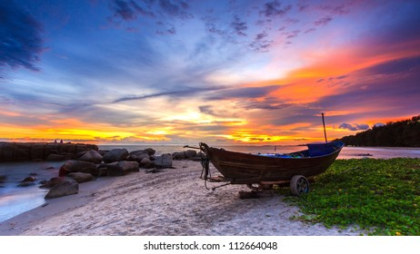 The boat on beach in sunset time.
