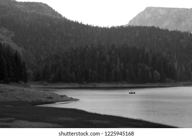 Boat on Black Lake at National Park Durmitor. Summer black and white landscape. Montenegro